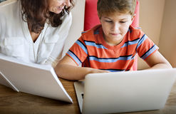 家庭使用数字式膝上型计算机概念的母亲儿子 库存照片