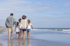 家庭做父母走在海滩的女孩孩子 免版税图库摄影