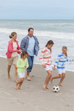 家庭做父母踢海滩足球橄榄球的孩子 库存图片