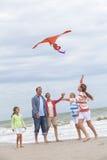 家庭做父母飞行在海滩的女孩孩子风筝 免版税图库摄影