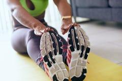家庭做锻炼的健身黑人妇女舒展在垫 免版税库存照片