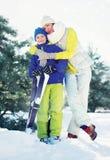 家庭健康生活方式!在冬天森林里照顾拥抱有滑雪的儿子孩子 免版税库存图片
