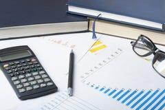 家庭储蓄,预算概念 图、帐薄、笔、计算器和玻璃在木办公室桌上 免版税图库摄影