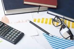 家庭储蓄,预算概念 图、帐薄、笔、计算器和玻璃在木办公室桌上 图库摄影