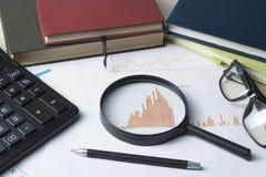 家庭储蓄,预算概念 图、玻璃、笔、计算器和放大镜在木办公室桌上 免版税库存图片