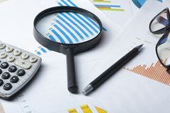 家庭储蓄,预算概念 图、玻璃、笔、计算器和放大镜在木办公室桌上 免版税库存照片