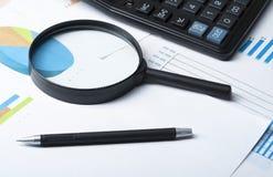 家庭储蓄,预算概念 图、笔、计算器和放大镜在木办公室桌上 图库摄影