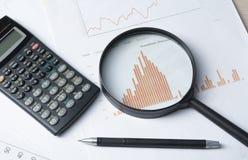 家庭储蓄,预算概念 图、笔、计算器和放大镜在木办公室桌上 免版税库存照片