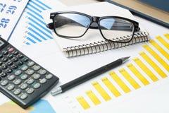 家庭储蓄,预算概念 图表 笔、计算器和玻璃在木办公桌桌上 图库摄影