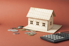 家庭储蓄,预算概念 式样房子、笔记薄、笔、计算器和硬币在木办公桌桌上 免版税库存照片