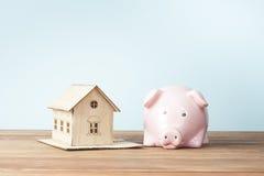 家庭储蓄,预算概念 式样房子、笔记薄、笔、计算器和硬币在木办公桌桌上 免版税库存图片