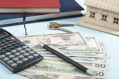 家庭储蓄,预算概念 式样房子、笔记薄、笔、计算器和金钱在木办公桌桌上 库存照片
