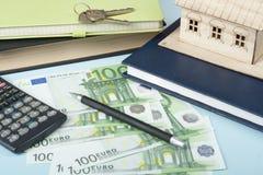 家庭储蓄,预算概念 式样房子、笔记薄、笔、计算器和金钱在木办公桌桌上 图库摄影