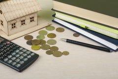 家庭储蓄,预算概念 式样房子、笔记薄、,计算器、笔和硬币在木办公桌桌上 库存图片