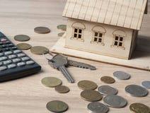 家庭储蓄,预算概念 式样房子、钥匙、计算器和硬币在木办公室桌上 库存照片