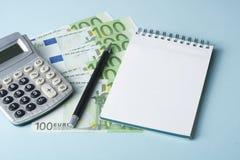 家庭储蓄,预算概念 笔记薄、笔、计算器和金钱在木办公桌桌上 免版税库存照片