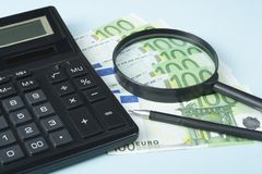 家庭储蓄,预算概念 计算器、笔、金钱和放大镜在木办公室桌上 图库摄影