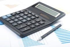家庭储蓄,预算概念 计算器、笔和图在办公室桌上 免版税库存照片