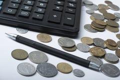 家庭储蓄,预算概念 计算器、笔和硬币在办公室桌上 免版税库存图片
