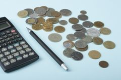 家庭储蓄,预算概念 计算器、笔和硬币在木办公桌桌上 免版税库存图片