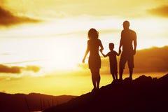家庭儿子日落现出轮廓天空 免版税库存图片