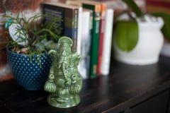 家庭内部装饰、Ganesh一个陶瓷小雕象,书和花盆有植物的黑木洗脸台的 库存图片