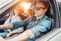 年轻家庭到在旅行期间的汽车里 免版税库存照片
