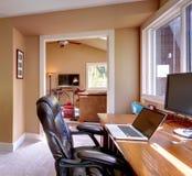 家庭办公和与棕色墙壁的计算机和椅子。 库存照片