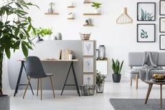 家庭办公室内部的真正的照片与客厅的 现代家具和绘画在墙壁上 免版税库存图片