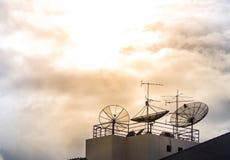 家庭卫星盘和天线在大厦顶部 免版税库存照片