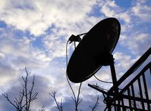 家庭卫星盘天线剪影在阳台的有分类的 图库摄影