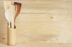 家庭厨房装饰:在一个竹容器的葡萄酒利器在木板背景,舒适安排土气样式 免版税图库摄影