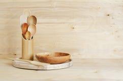家庭厨房装饰:木利器,在一个竹容器的匙子在木板背景,土气样式 库存图片