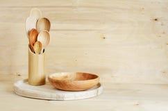 家庭厨房装饰:木利器,在一个竹容器的匙子在木板背景 土气样式 免版税库存照片