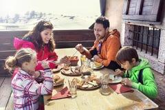 家庭吃午餐在山的瑞士山中的牧人小屋 库存图片