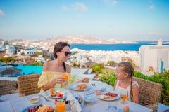家庭吃早餐在室外咖啡馆有惊人的看法 可爱的吃在豪华旅馆的女孩和母亲新月形面包 图库摄影