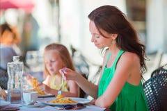 家庭吃晚餐在与意大利菜单的室外咖啡馆 可爱的吃在豪华旅馆的女孩和母亲意粉 免版税库存照片