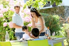家庭吃烤肉午餐在庭院 库存图片