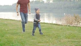 家庭和儿童概念 愉快的父亲和儿子获得乐趣在夏天公园 股票录像