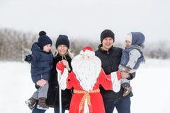 年轻家庭和圣诞老人雪场面的 库存图片