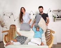 年轻家庭和在家战斗与枕头的两儿童游戏 免版税库存图片