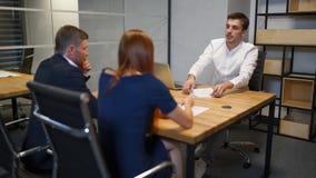 家庭和地产商商人在会议室里谈论关于抵押合同 影视素材