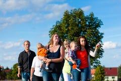 家庭和多代-在草甸的乐趣在夏天 免版税库存照片