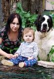 家庭和爱宠爱与母亲的概念画象,并且女婴是坐和使用与狗在庭院里户外 免版税库存图片