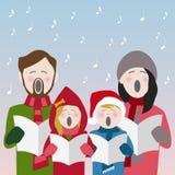 家庭唱歌在雪的圣诞节颂歌 免版税库存照片