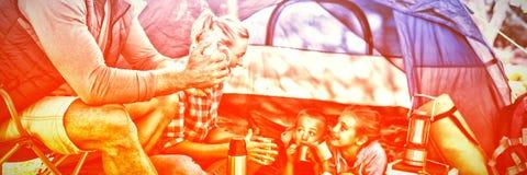家庭喝快餐和咖啡在帐篷之外在露营地 图库摄影