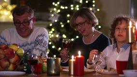 家庭圈子的愉快的妇女在圣诞节桌上 感恩的大家庭 照明设备,在的蜡烛 股票视频