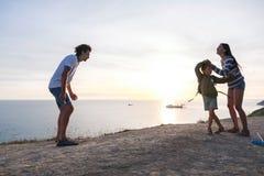 家庭在一座山的乐趣消遣有海边视图 爸爸、妈妈和儿子舞蹈在日落 侧视图 免版税库存照片
