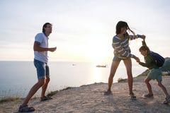 家庭在一座山的乐趣消遣有海边视图 爸爸、妈妈和儿子舞蹈在日落 库存照片
