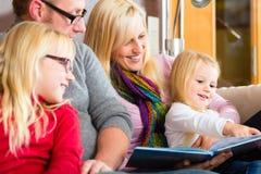 家庭在书的读书故事在沙发在家 免版税库存照片